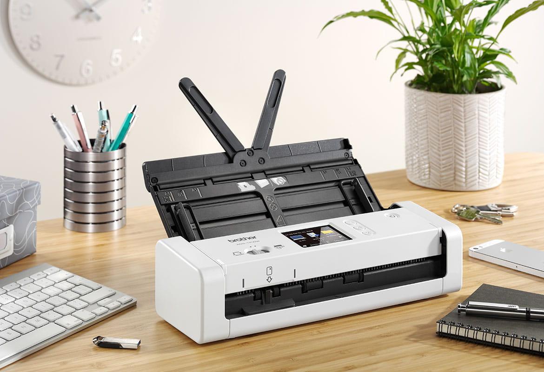 Brother ADS-1700W компактен скенер за документи, на дървено бюро, растение и клавиатура