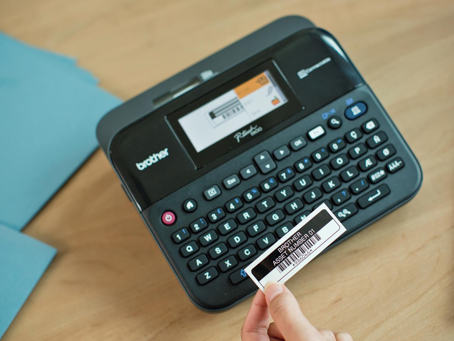 Brother P-touch D600 label printer with asset label being held in hand