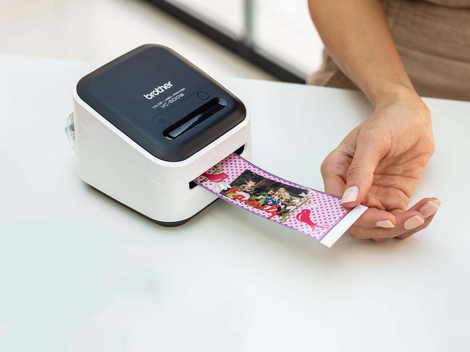 Цветен етикетен принтер Brother отпечатва широк етикет с графика и снимка