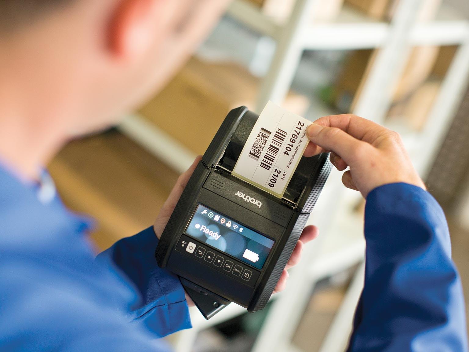 Служител в склад държи в ръка етикетен принтер серията RJ, докато се отпечатва етикет