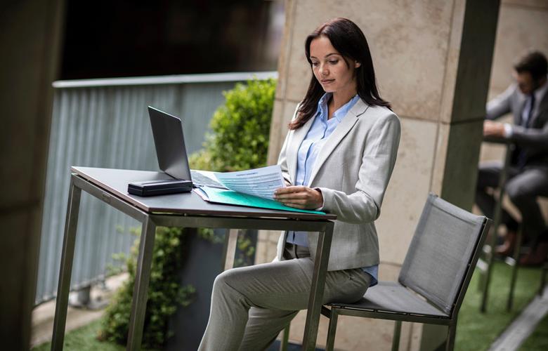 Жена в кафене разглежда документи, лаптоп и мобилен принтер на масата