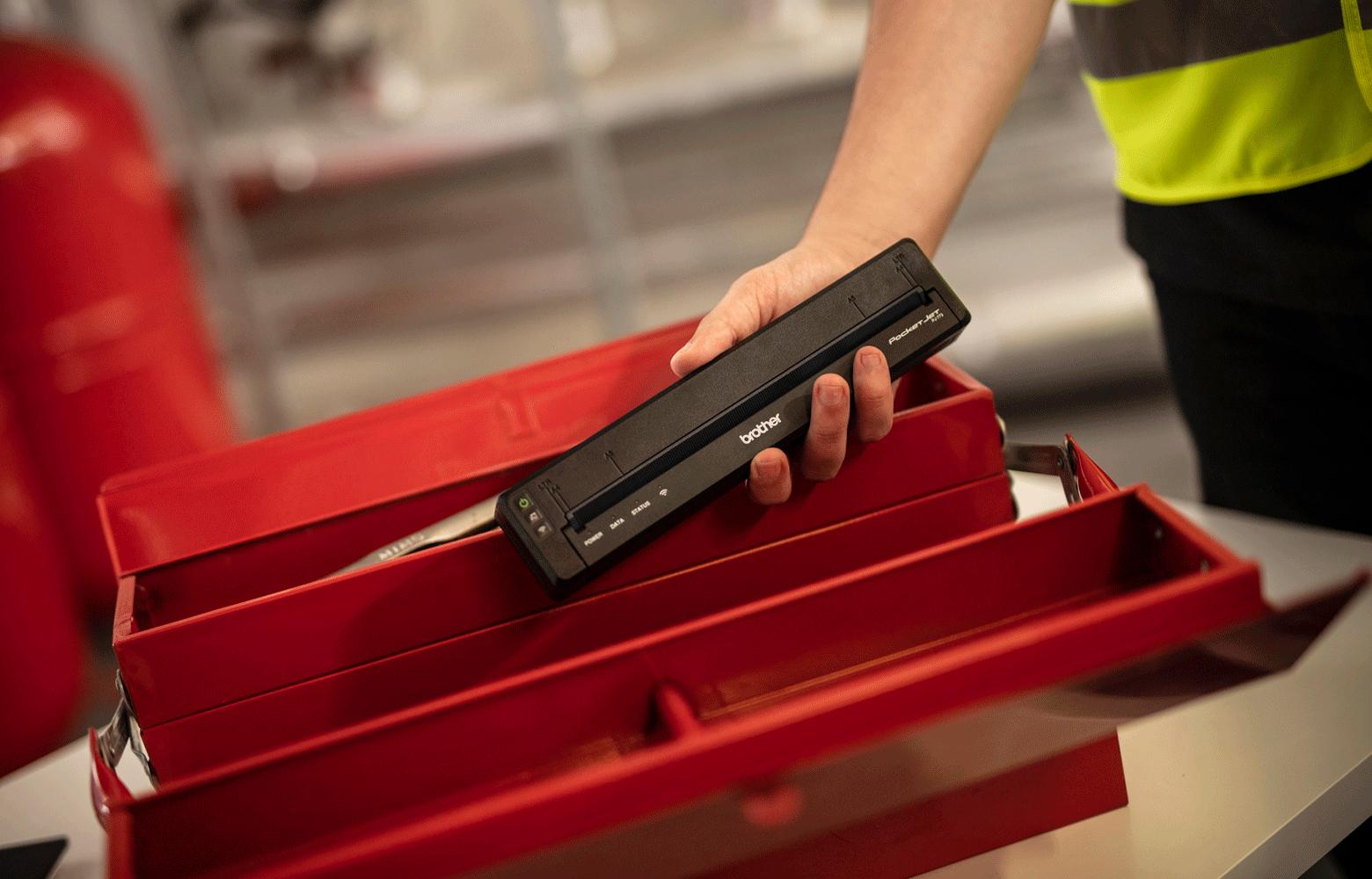 Работник поставя мобилен принтер в кутия за инструменти