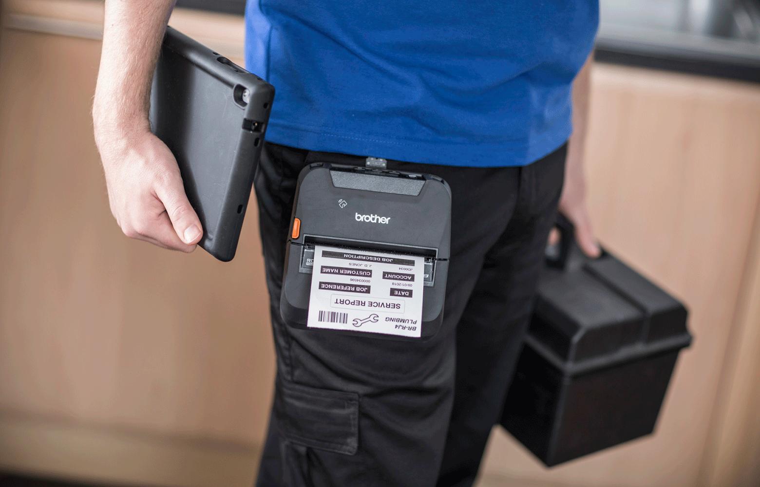 Работник в синя тениска, държи кутия за инструменти, таблет и RJ принтер с щипка за колан