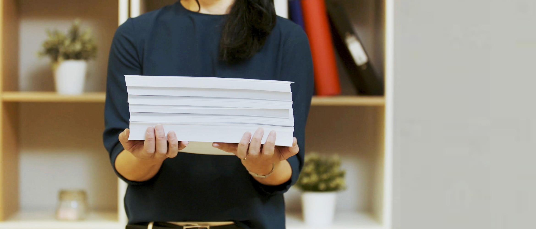 Жена пренася куп с хартия