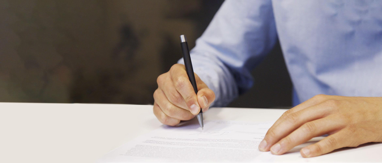Човек облечен в синя риза, подписва документ