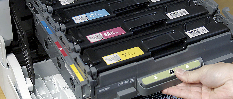 Човек изважда тонер касетите от принтер