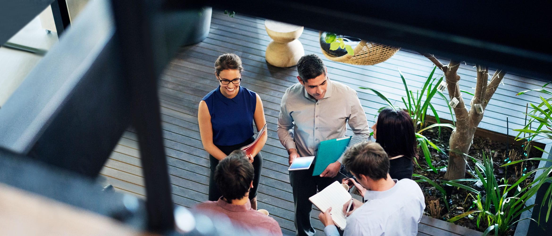 Петима служители на работното място на бъдещето провеждат неформална стендъп бизнес среща в офиса.