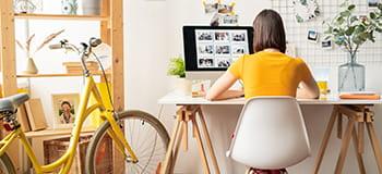жена седи на бюрото, с жълт велосипед до нея