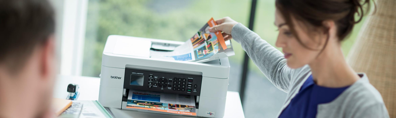 Жената седеи на бюро,взема документ от принтера