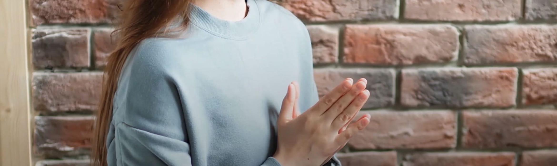Жената седи със събрани ръце