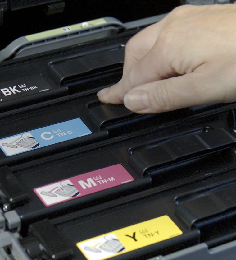 Служител поставя тонер касета в устройството