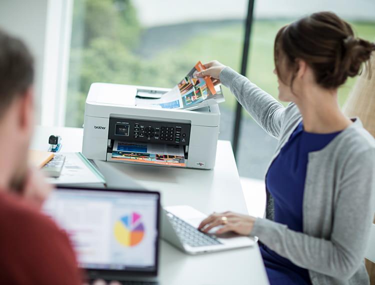 Жена в домашнен офис стои до принтера