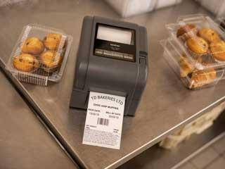 Принтер за етикети Brother TD-4D на стоманена маса до торти в пекарна