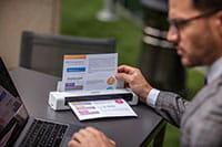 Мъж с очила, седи на открито, използва лаптоп и документен скенер Brother DSmobile DS740D с цветен A4 документ