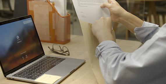 Moški sedi za mizo s prenosnim računalnikom in vstavlja dokumente v kuverto